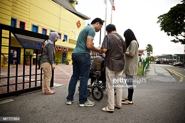 Citizens show their polling cards and identity cards to the presiding officers outside the Siglap Community Centre one of the polling stations during...