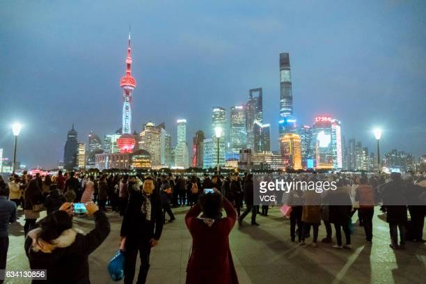 Citizens take photos of the Oriental Pearl Tower which lights up in red to brace for the upcoming Valentine's Day on February 7 2017 in Shanghai...