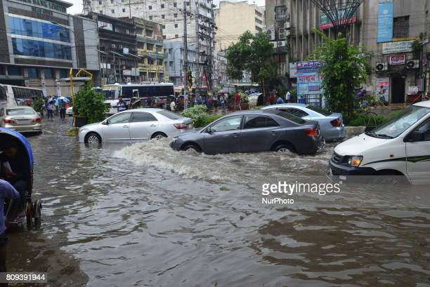 Citizens Vehicles and Rickshaws try driving with passengers through the flooded streets of Dhaka city after heavy downpour caused almoststandstill on...