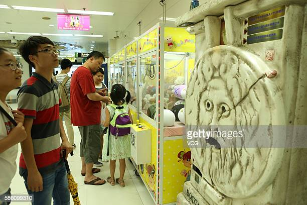 Citizens view a fortunetelling machine at an underground mall in People's Square on August 4 2016 in Shanghai China Only three coins one can receive...