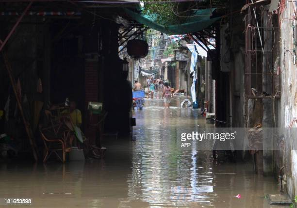 Citizens walk in a flooded residential area in Shantou south China's Guangdong province on September 23 2013 after Typhoon Usagi landed in...