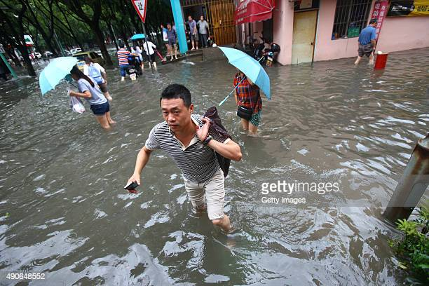 Citizens walk in ponding brought by the typhoon Dujuan on September 30, 2015 in Ningbo, Zhejiang Province of China. Typhoon Dujuan made landfall in...