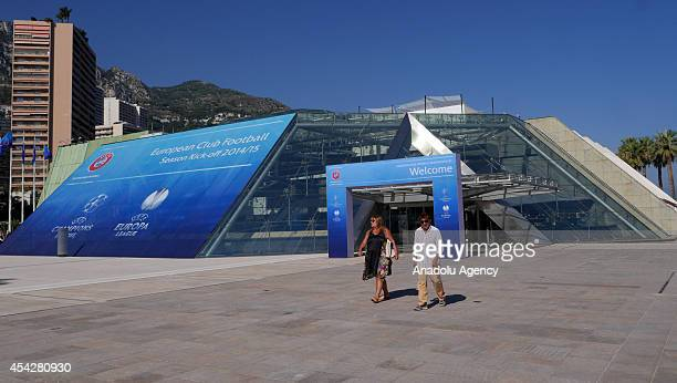 Citizens walk past in front of the placard prior to the UEFA Champions League draw at the Grimaldi Forum building in Monaco on August 27 2014 The 32...