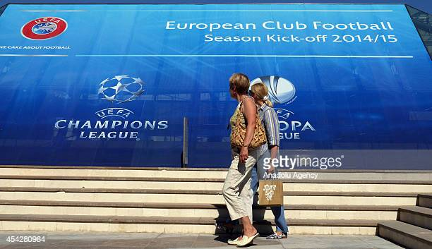 Citizens walk past in front of the placard prior to the UEFA Champions League draw in Monaco on August 27 2014 The 32 clubs 22 of which qualified...