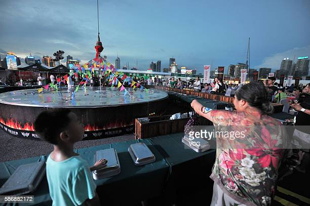 Citizens watch a large cauldron in which 24 kinds of seafood are cooked during the 8th Qingdao International Sailing Week Qingdao International...