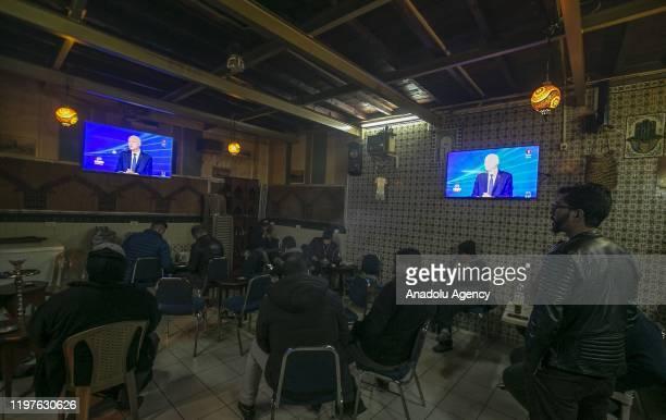 Citizens watch Tunisian President Kais Saied on television as he makes evaluations regarding the agenda, including U.S. President Donald Trumpâs...