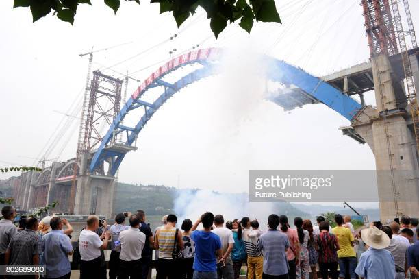 Citizens watch workers join the two sections of the main arch of a bridge under construction on June 28 2017 in Yibin China The doubledecker bridge...