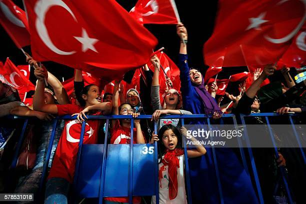 Citizens wave Turkish Flags as they gather at Konak Square during a demonstration staged to protest and to show solidarity against Parallel...