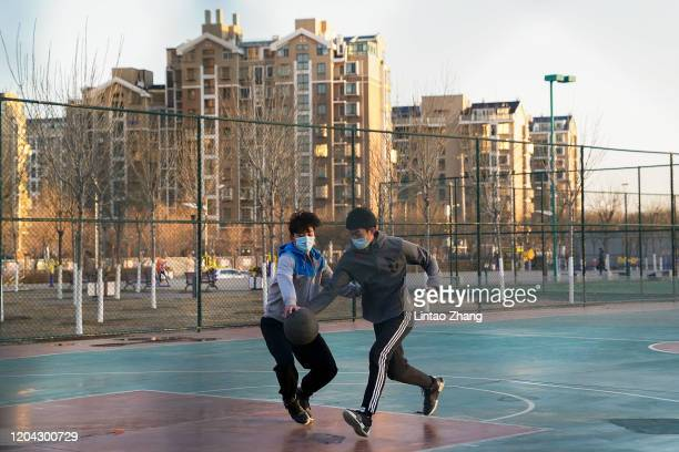 Citizens wear a protective facemasks as they play basketball at a park in Beijing on February 29, 2020 in Beijing, China. The number of cases of a...