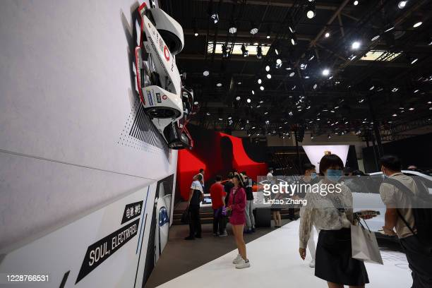 Citizens wear protective masks as they visit the Porsche booth during the 2020 Beijing International Automotive Exhibition at China International...