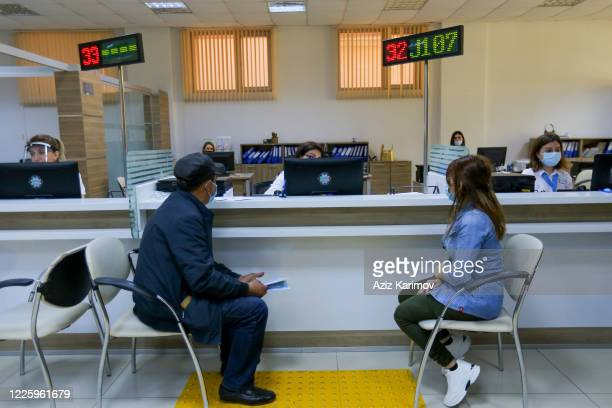 Citizens wearing a protective facemask and keep a social distance from each other while queuing inside ASAN service in Baku on May 20 2020 in Baku...