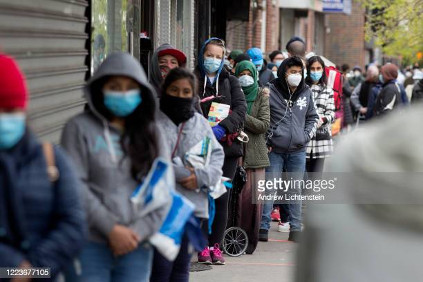 Citizens wearing protective masks form lines to receive free food from a food pantry run by the Council of Peoples Organization on May 8 2020 in the...