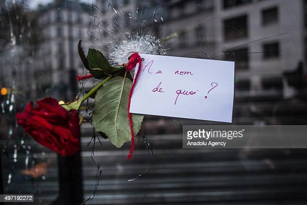 Citizens who gathered around 'La Belle Equipe' restaurant leave a flower and note saying 'What for' to a bullet hole in Paris France on November 14...