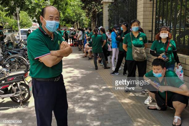 Citizens who visited or live near Xinfadi Market queue for a nucleic acid test at a sports center on June 16 2020 in Beijing China From June 11 to...
