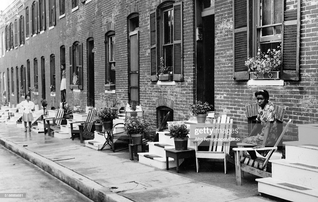 Citizens, with row houses, cleaning during the Afro American Newspapers Clean Block urban beautification campaign, Baltimore, Maryland, 1955.
