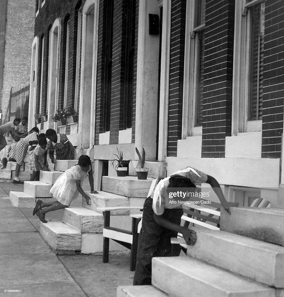 Citizens, with row houses, cleaning during the Afro American Newspapers Clean Block urban beautification campaign, Baltimore, Maryland, June 28, 1945.
