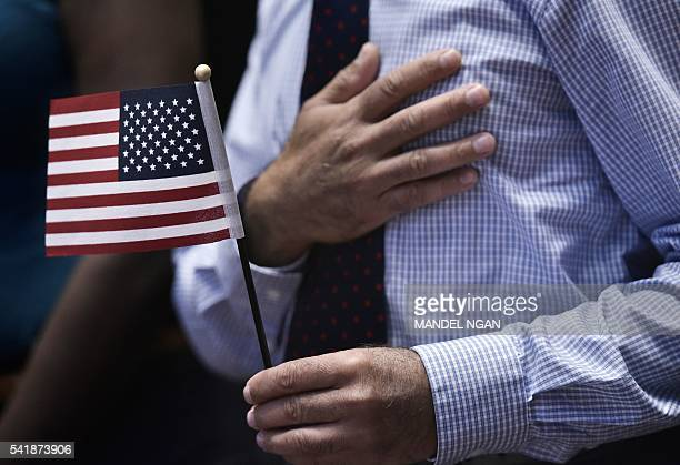 A citizenship candidate listens to the National Anthem during a naturalization ceremony on World Refugee Day in recognition of those who have come to...