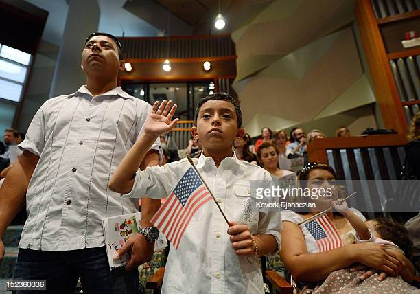 S citizenship candidate Ricardo Barrera takes the oath of citizenship as his father Ricardo Barrera mother Reina Barrera and his sister Ashley look...