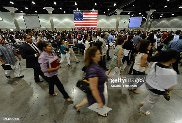 S citizenship candidates rush over to pick up their certificates after taking the oath of citizenship at a naturalization ceremony at the Los Angeles...