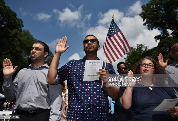 Citizenship candidates take the Oath of Allegiance in a naturalization ceremony at George Washington's Mount Vernon estate during Independence Day...