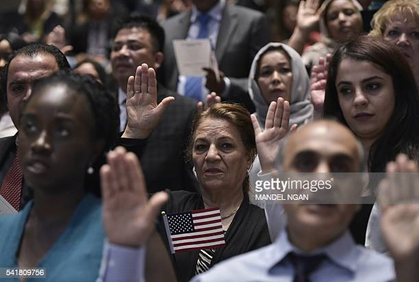 Citizenship candidates take the Oath of Allegiance to the US during a naturalization ceremony on World Refugee Day in recognition of those who have...
