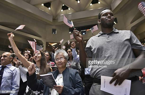 Citizenship candidates wave US flags after taking the Oath of Allegiance to the US during a naturalization ceremony on World Refugee Day in...