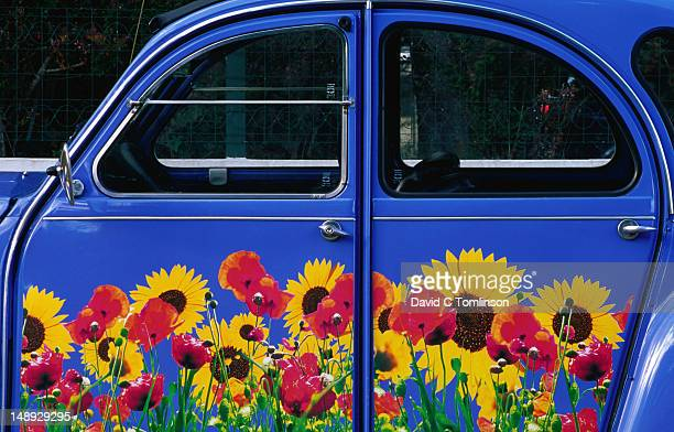 Citroen 2CV covered in design of sunflowers and poppies, Lot region.