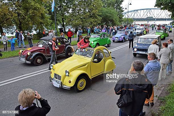 Citroen 2CV vehicles driving on the street during the parade