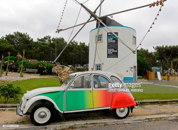 Citroen classic 2CV painted with Portuguese flag colours is parked near a traditional wind mill at Ericeira village during the World 2017 2CV Meeting...