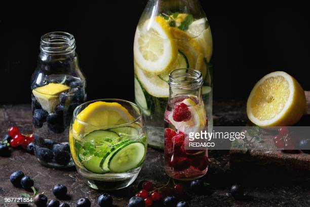 Citrus cucumber berries blueberry and raspberry sassy sassi water for detox in glass bottles on dark black background Clean eating healthy lifestyle...