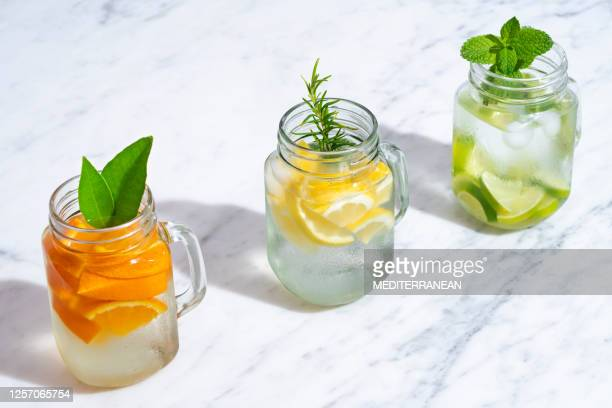 citrus infused water non alcohol cocktails with orange, lemon and lime - infused water stock pictures, royalty-free photos & images