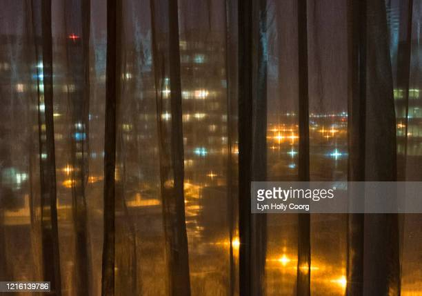 city at night seen through sheer curtains - lyn holly coorg stock pictures, royalty-free photos & images