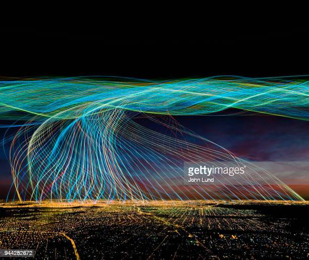 city at night with streaming data overhead - john lund stock pictures, royalty-free photos & images