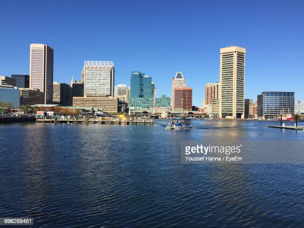 city at waterfront against blue sky - baltimore stock photos and pictures