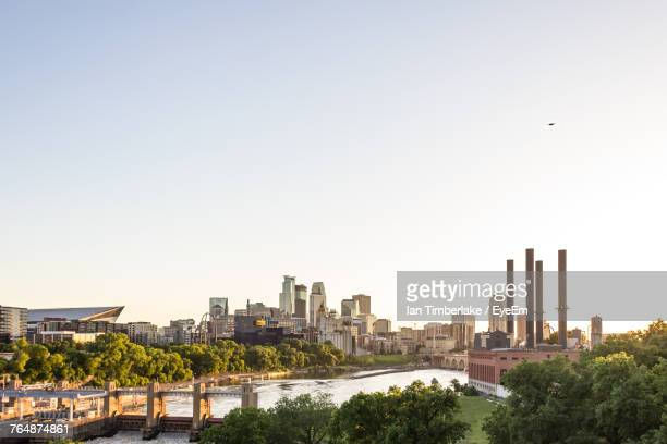city at waterfront against clear sky - minneapolis stock photos and pictures