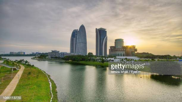 city at waterfront against cloudy sky - putrajaya stock photos and pictures