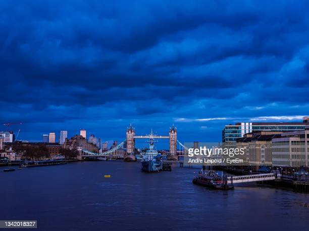 city at waterfront against cloudy sky - premiere stock pictures, royalty-free photos & images