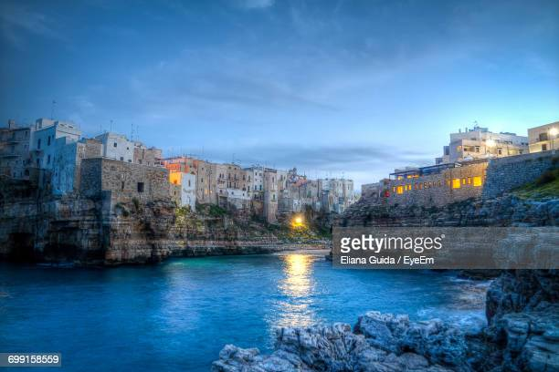 city at waterfront against cloudy sky - bari stock photos and pictures