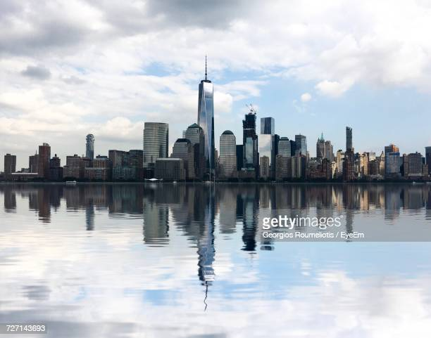 city at waterfront against cloudy sky - new york skyline stock photos and pictures