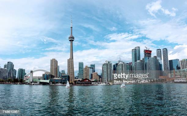 city at waterfront against cloudy sky - toronto stock pictures, royalty-free photos & images
