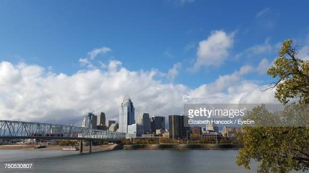 city at waterfront against cloudy sky - cincinnati stock pictures, royalty-free photos & images
