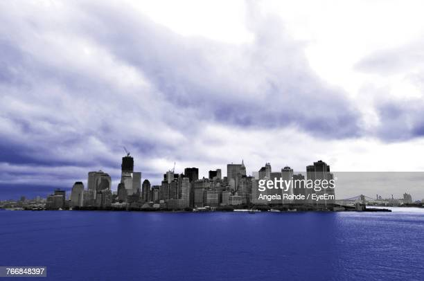 city at waterfront against cloudy sky - angela rohde stock-fotos und bilder