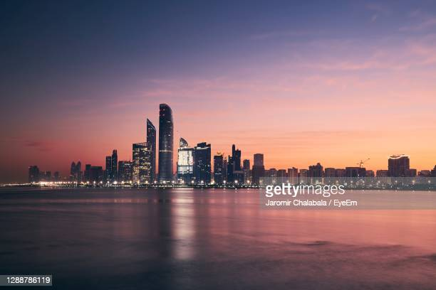 city at waterfront during sunset - abu dhabi stock pictures, royalty-free photos & images