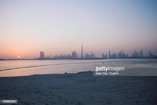 city at waterfront during sunset - twilight stock pictures, royalty-free photos & images