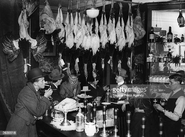 A city bar in London at Christmas with plucked turkeys hanging overhead