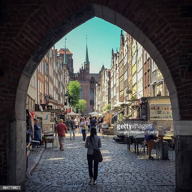 City Buildings And People Seen Through Archway Against Blue Sky