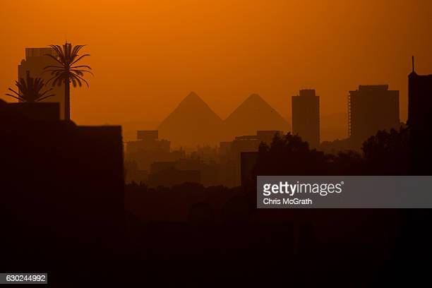 City buildings are seen in front of the famous Giza Pyramids on December 15 2016 in Cairo Egypt Since the 2011 Arab Spring Egyptians have been facing...
