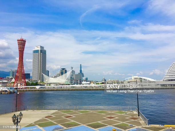 city buildings by river against cloudy sky - 兵庫県 ストックフォトと画像