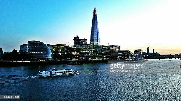 City Buildings By River Thames Against Sky