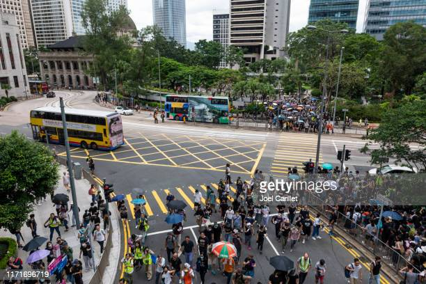 city buses and protest crowds in hong kong's central district - protestor stock pictures, royalty-free photos & images